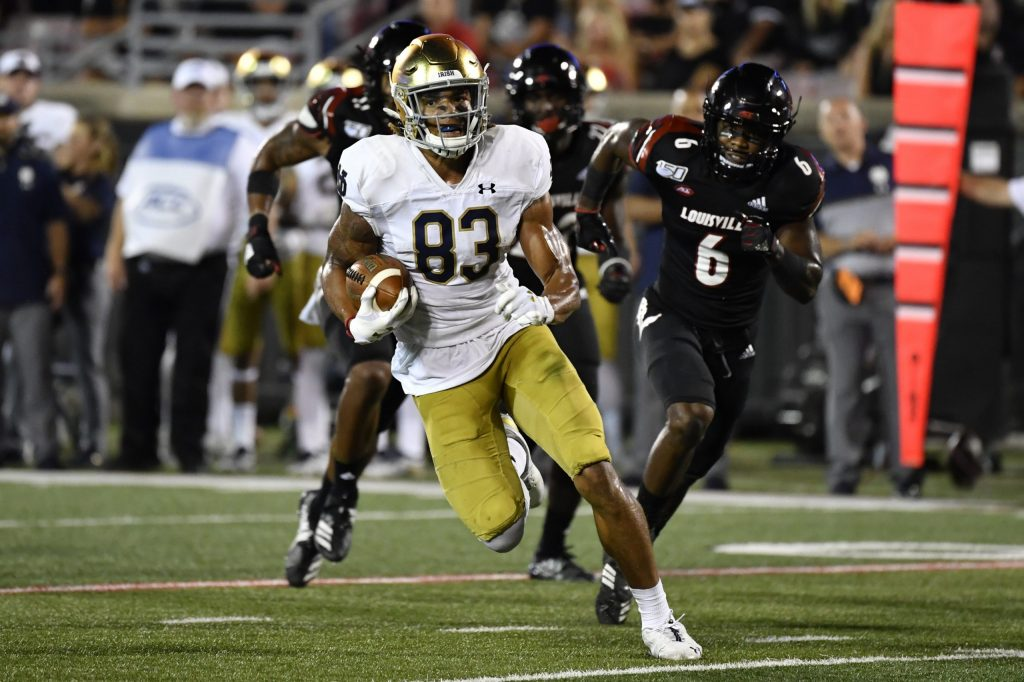 CORRECTS PLAYER TO NOTRE DAME'S CHASE CLAYPOOL (83) INSTEAD OF LOUISVILLE TIGHT END MARSHON FORD Notre Dame's Chase Claypool (83) runs from the pursuit of Louisville defensive back Cornelius Sturghill (6) during the second half of an NCAA college football game in Louisville, Ky., Monday, Sept. 2, 2019. Notre Dame won 35-17. (AP Photo/Timothy D. Easley)