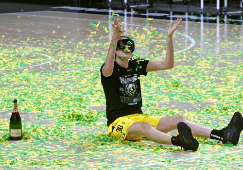 Seattle Storm forward Breanna Stewart celebrates after her team wins the championship, with confetti flying down as a champagne bottle sits beside her.