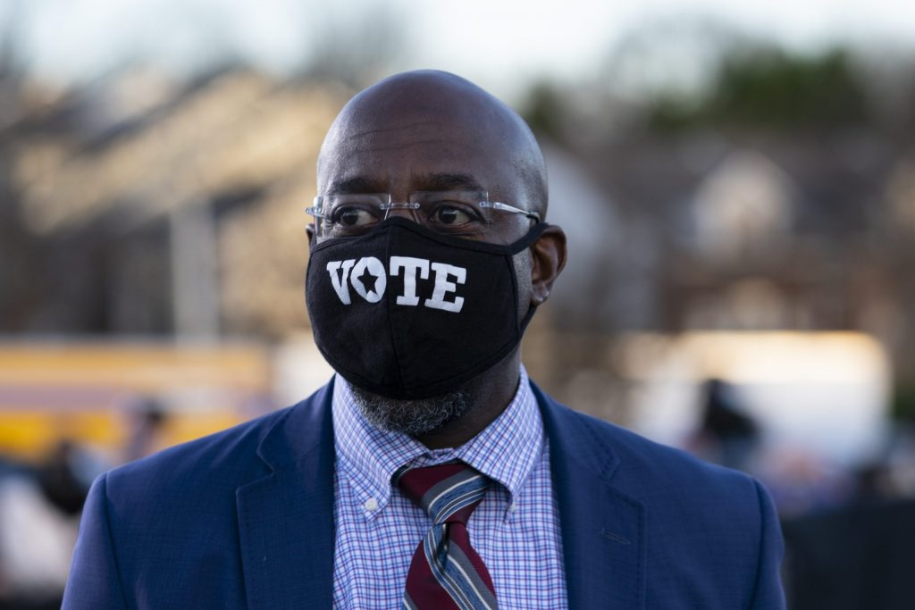 Georgia Democratic candidates for U.S. Senate, Rev. Raphael Warnock walks from the stage during a campaign event with President-elect Joe Biden in Atlanta, Monday, Jan. 4, 2021. (AP Photo/Carolyn Kaster)